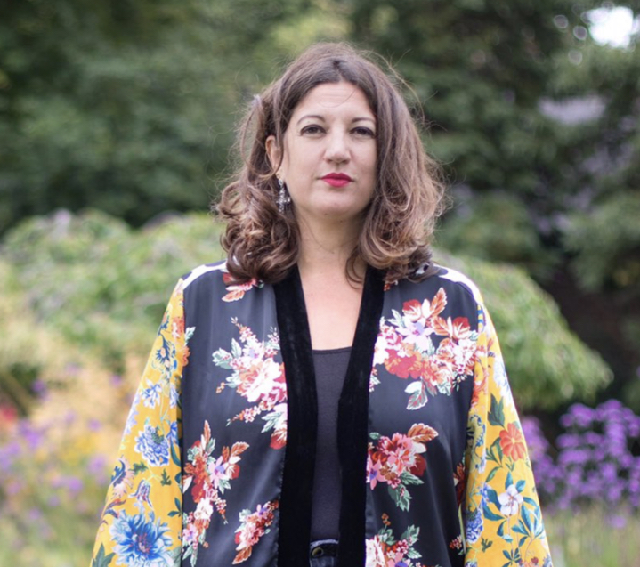 Polly Brannan stands in floral attire surrounded by flowers and greenery.