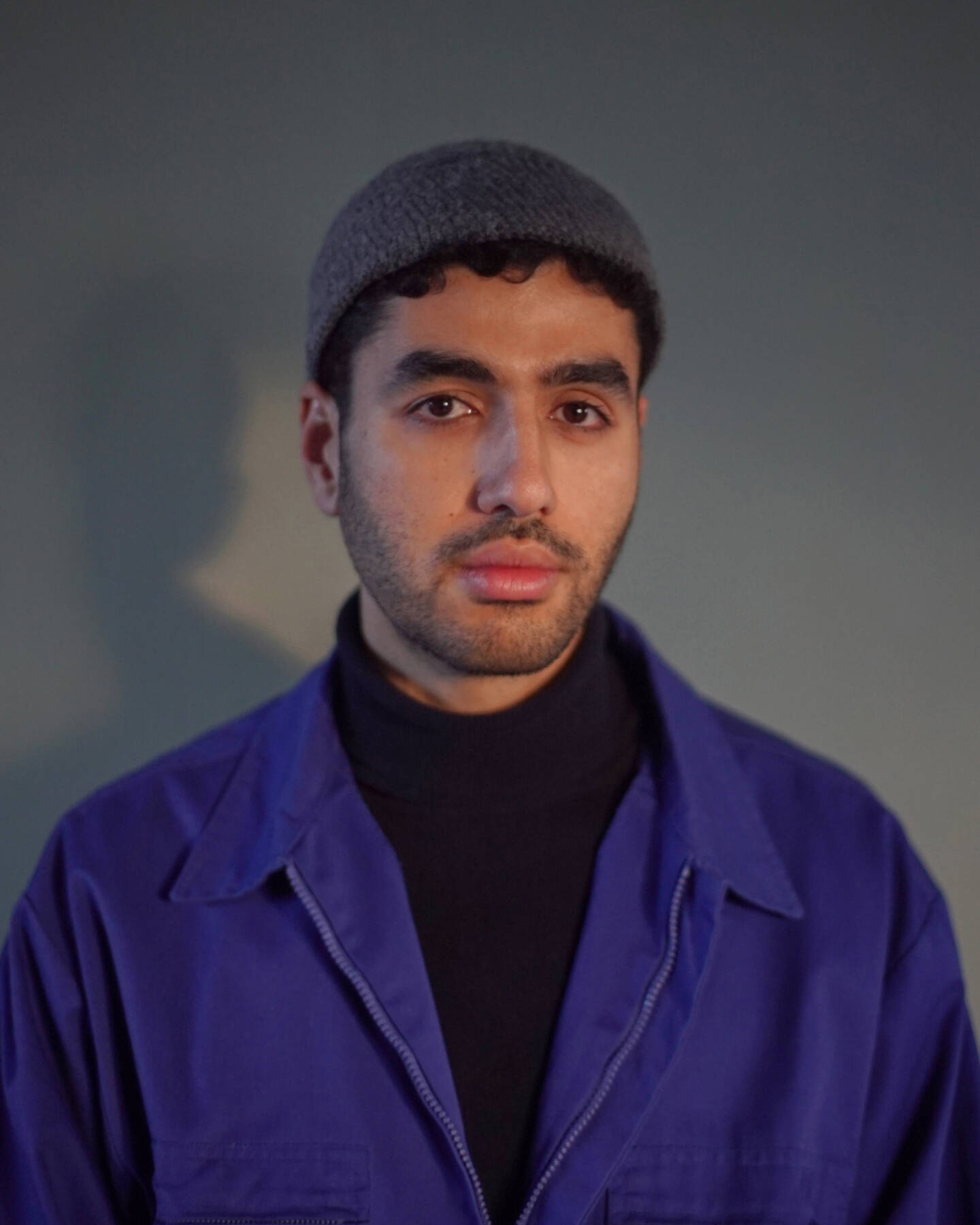 Hicham in a blue jacket and grey skull cap.