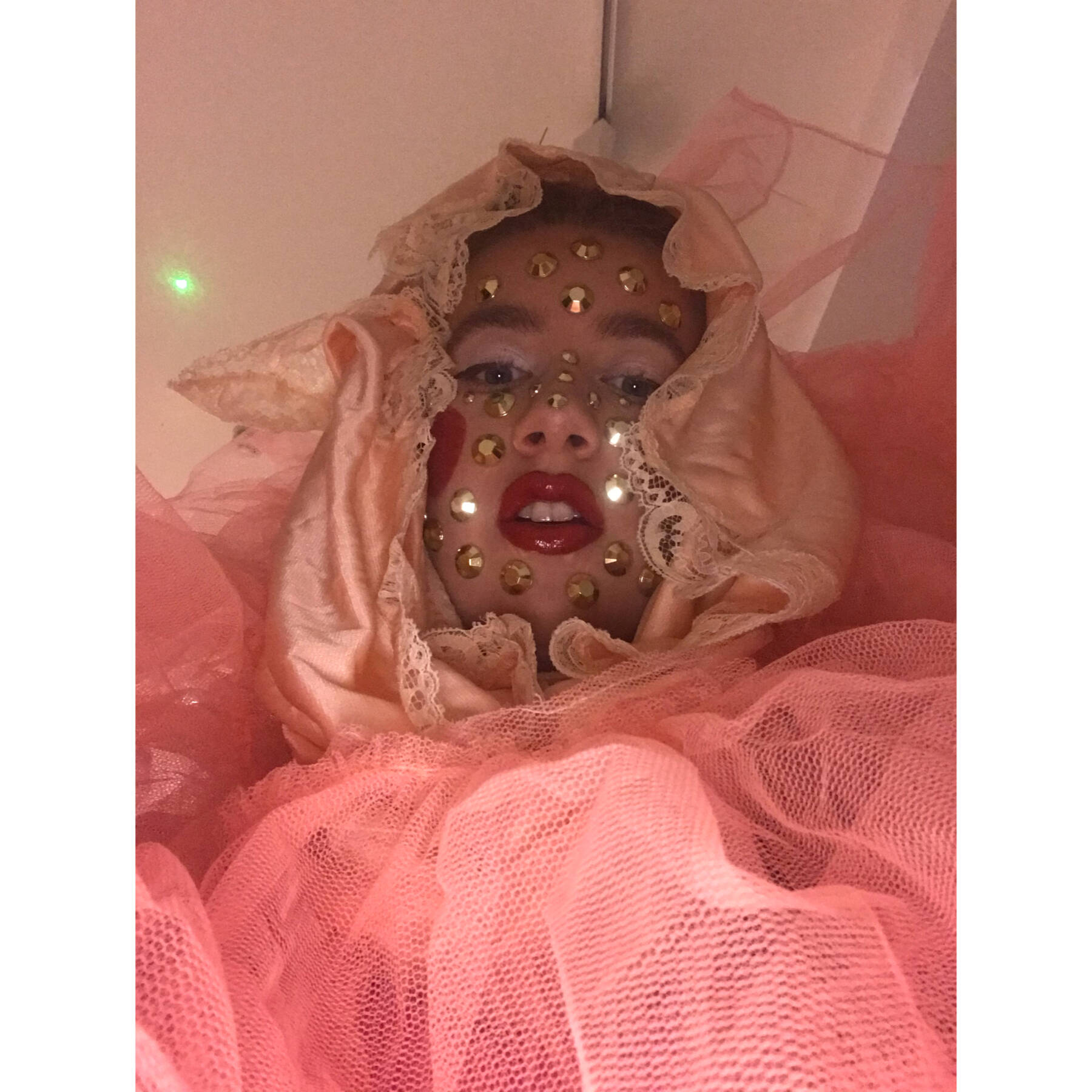 Moina wrapped in pink fabrics with gold sequins stuck all over her face.
