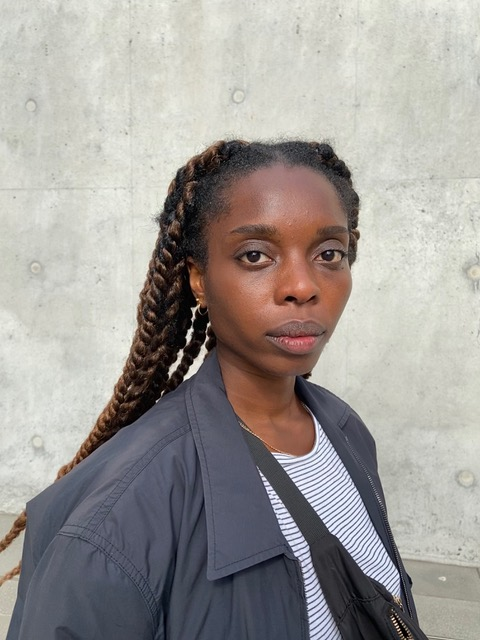 Tolu standing against a grey concrete background.