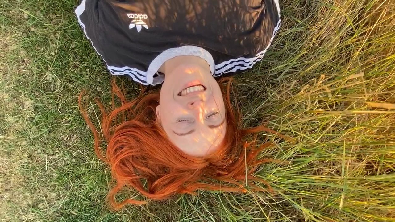 Suzy lies on a patch of grass while smiling with eyes closed.