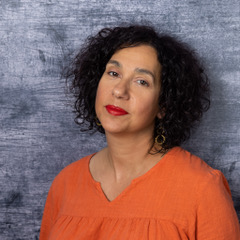 Natalie Ross wearing an orange top and standing against a blue and white background.